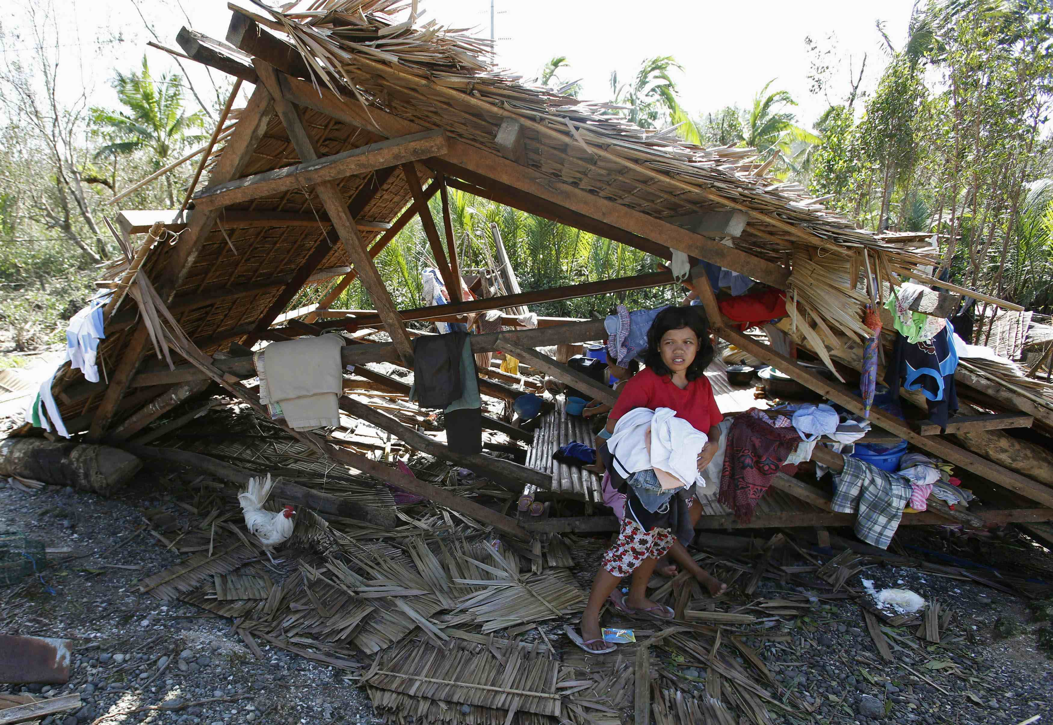 A typhoon victim walks in front of her house swept by Typhoon Hagupit in Can-avid, Samar